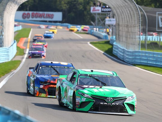 Aug 5, 2018; Watkins Glen, NY, USA; Monster Energy NASCAR Cup Series driver Kyle Busch (18) and Monster Energy NASCAR Cup Series driver Chase Elliott (9) during the Go Bowling at The Glen at Watkins Glen International. Monster Energy NASCAR Cup Series driver Chase Elliott (9) won the race. Mandatory Credit: Kevin Hoffman-USA TODAY Sports