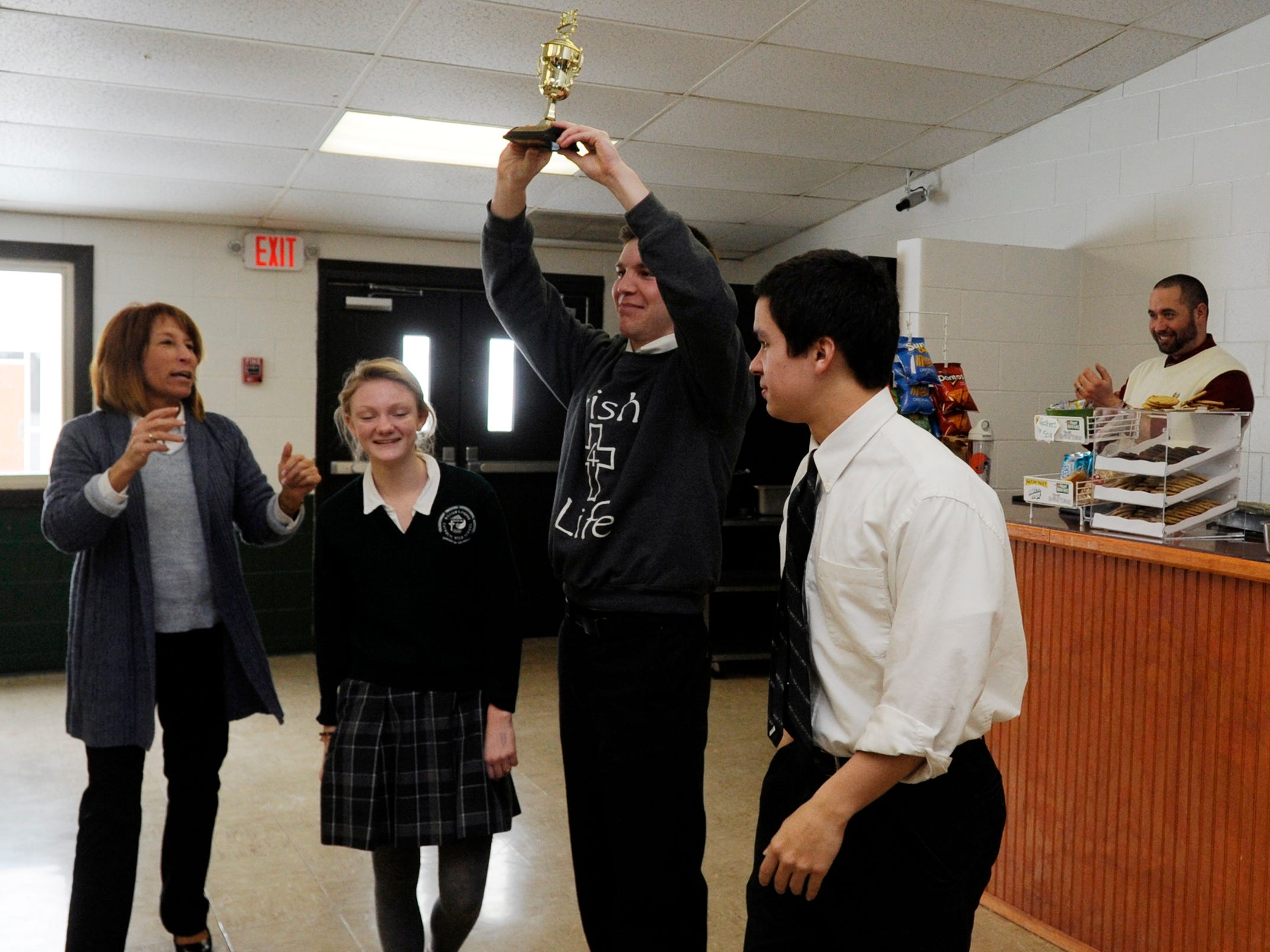 Eli Frazier holds up the 2015 Lancaster Eagle-Gazette Battle of the Fans Champion trophy Wednesday in the Fisher Catholic High School cafeteria in Lancaster.