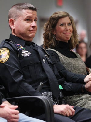 Tallahassee Police Department Officer Scott Angulo holds hands with his wife, Elizabeth, at a Tallahassee City Commission meeting earlier this month.  Angulo was named Officer of the Year by the International Association of Chiefs of Police for his bravery on Nov. 22, 2014, when he took down a gunman on Caracus Court.