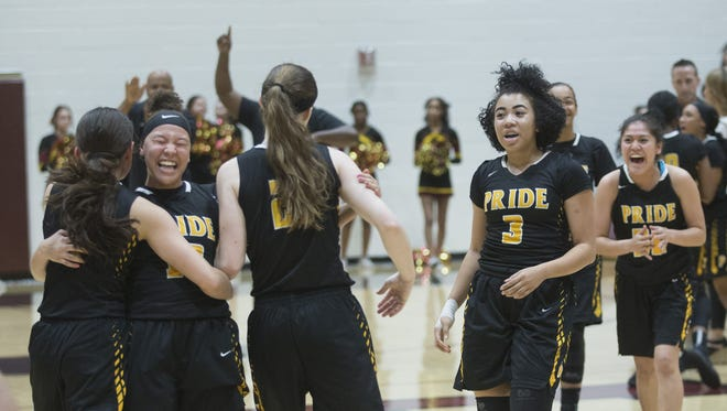 Mountain Pointe teammates charge the court after upsetting Hamilton during the second round of the 6A Conference girls basketball state tournament on February 17, 2017 at Chandler Hamilton High School in Chandler, Ariz.