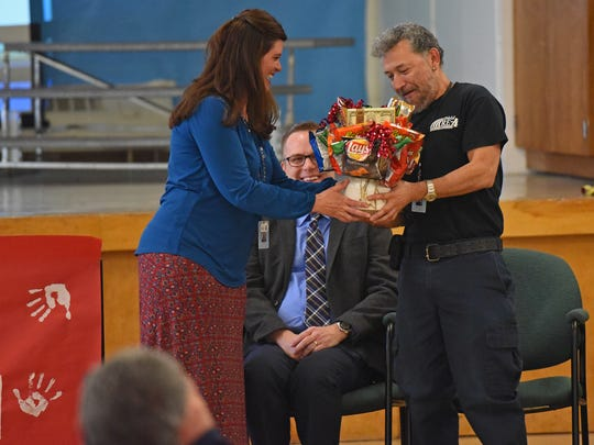 Tozer Elementary School janitor Rudy Hernandez receives a gift from school principal Shelly Butcher honoring Hernandez for being named top 10 finalist in Janitor of the Year Contest sponsored by the Cintas Corporation.