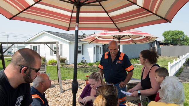 Mark Feller, second left, and his family run their business, Feller's Towing & Recovery, beneath a patio umbrella the day after a fire demolished their garage workshop Most of their tools, three trucks, six motorcycles and anything else inside the building were totaled.