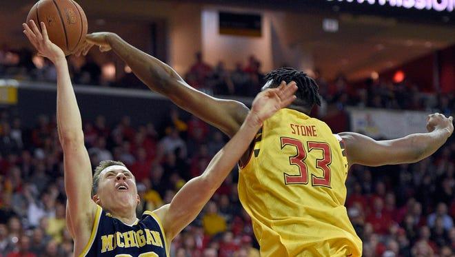 Michigan guard Duncan Robinson, left,  battles Maryland center Diamond Stone.