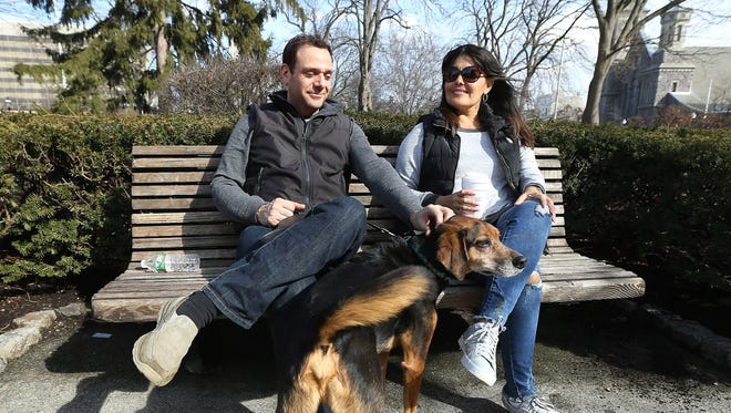 Morristown resident Brian Litwin, Paola Lopez of Peru and Tigger enjoy the unseasonably warm weather on the Morristown Green the day before a winter storm was predicted to dump close to a foot of snow on the area Feb. 9.