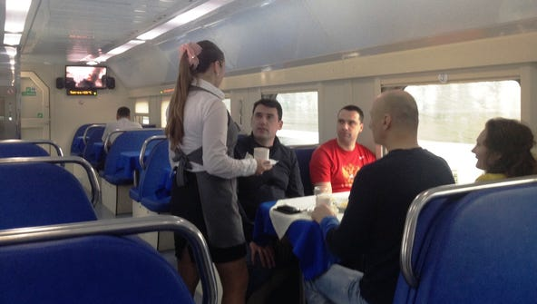 A Russian waitress serves travelers from Moscow to Sochi aboard  a special double-decker Olympics train on Feb. 18, 2014.