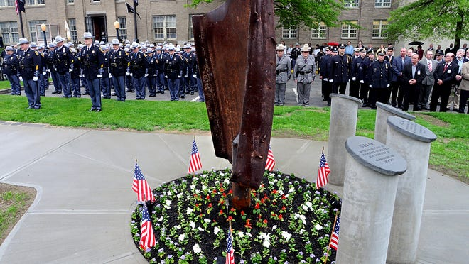 As flags fly at half-staff, members of the Dutchess County Sheriff's Office stand in formation Thursday behind the 9/11 memorial on the front lawn at department headquarters in Poughkeepsie. The steel beam was part of the World Trade Center towers.
