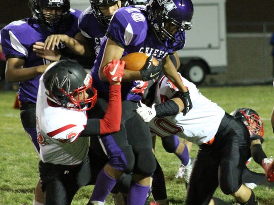 Mescalero's Aloysius Comanche tries to break free from two Mountainair defenders Friday night.