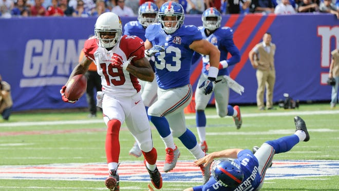 Arizona Cardinals Ted Ginn (19) breaks a tackle by New York Giants' Steve Weatherford (5) on his way to a touchdown during the second half  Sunday, Sept. 14, 2014, in East Rutherford, N.J.