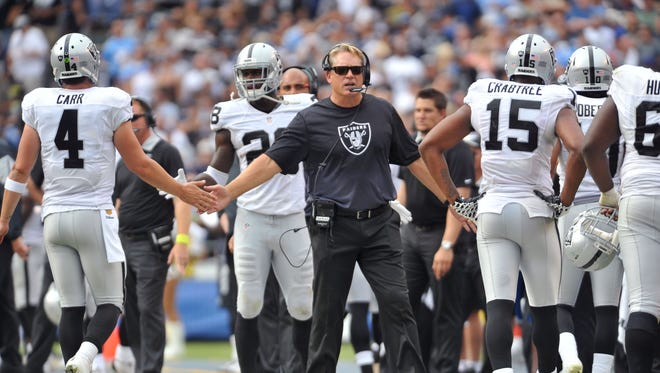 Oct 25, 2015; San Diego, CA, USA; Oakland Raiders head coach Jack Del Rio greets quarterback Derek Carr (4) and wide receiver Michael Crabtree (15) on the sideline during the second quarter in a game against the San Diego Chargers at Qualcomm Stadium.