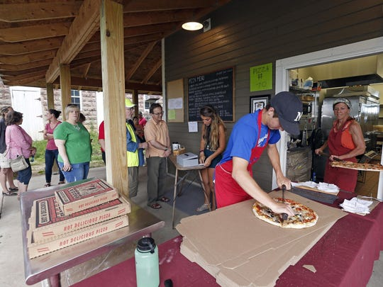 Johnny Pavak, right, boxes up a pizza as Tammy Winter, far right, brings out another wood-fired oven pizza at the Red Barn Farm near Northfield, Minn., where people gather to relax and enjoy pizza.