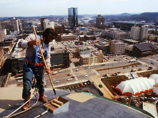 A worker applies gold paint to the roof of the Sunsphere
