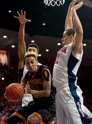 USC guard Jordan McLaughlin looks to pass the ball from under the basket as he's surrounded by UA forward Ryan Anderson (right) and guard Allonzo Trier during Sunday's game at McKale Center.