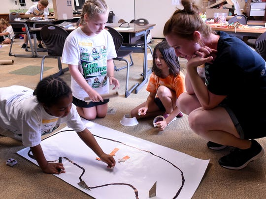 Campers Torie Davis, Izzy Barnhart, and Clara Yoder explain their track design to camp instructor and Coshocton Elementary reading interventionist Crlye Shaw during Camp Invention on Wednesday, June 20, 2018 at Coshocton Elementary School. Campers designed a path for a small robot to follow to activate a sensor.