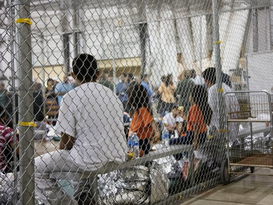 In this Sunday, June 17, 2018, photo provided by U.S. Customs and Border Protection, people who were taken into custody related to cases of illegal entry into the United States, sit in one of the cages at a facility in McAllen, Texas.