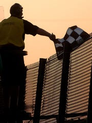 An official waves the checkered flag at Jackson Motor Speedway.