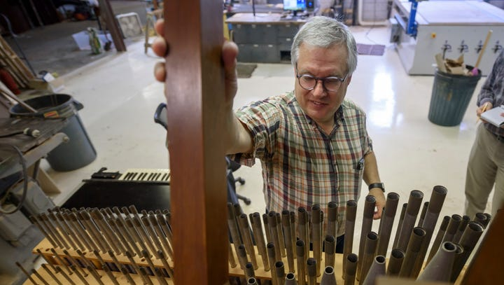 Rick Helderop inserts a wood pipe into an organ from