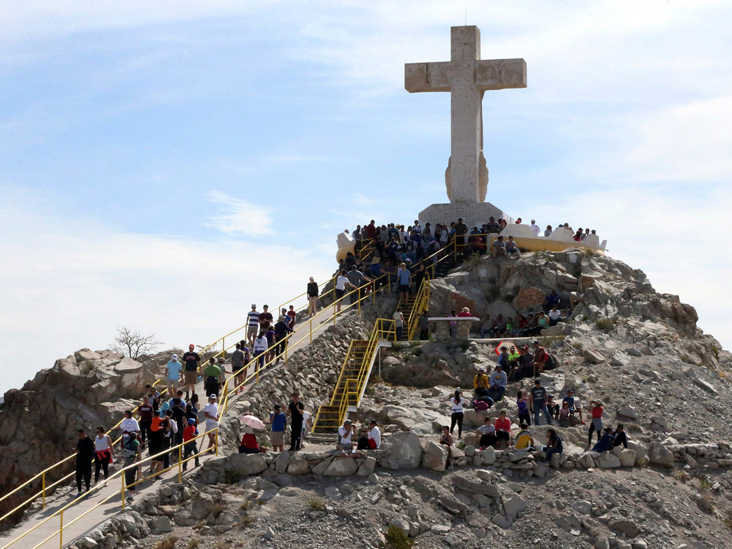 Pilgrims reach the base of the limestone cross atop