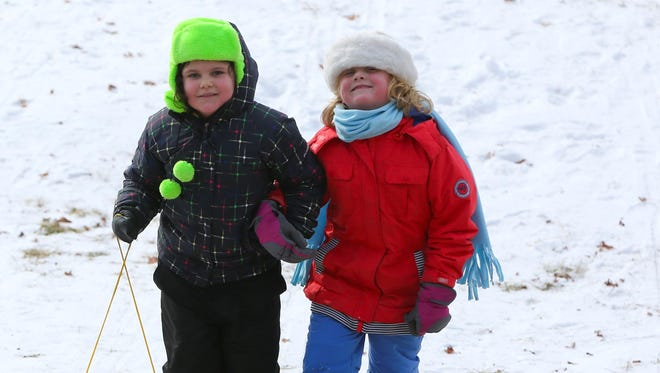 Two youngsters prepare to head back up Beach Front Hill at Hills Creek State during Winterfest 2015. Not much snow is needed for youngsters and adults to sled, saucer, toboggan, snowboard or ride a tube down the hill.
