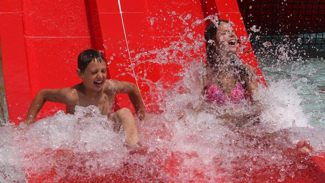 Cousins Tommy Renard, 10, of Marathon and Claire Krasowski, 15, of Wausau hit the water Wednesday as they go down one of the new slides at the grand reopening of Kaiser Pool in Wausau.