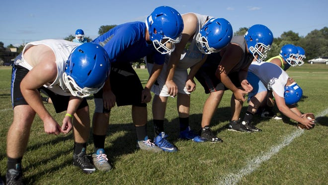 Assumption special teams players line up in a field goal formation on the first day of football practice at Assumption High School, Tuesday, Aug. 4, 2015.