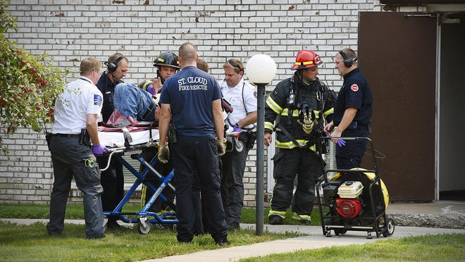 Rescue personnel from the St. Cloud Fire Department and Gold Cross Ambulance carry a man out of an apartment building and place him on a gurney Thursday at 1240 33rd Ave. N after a fire was reported in the building.