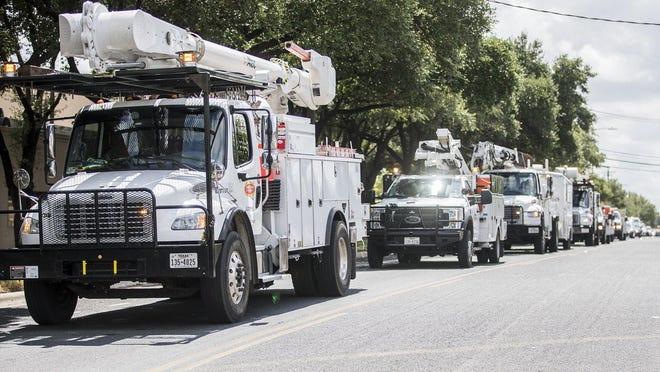 A long line of Austin Energy trucks carrying work crews deploys for two weeks to Mercedes to help with Hurricane Hanna restoration efforts on Monday.