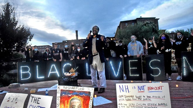 In this June 1 file photo, Rogers Johnson, president of the Seacoast NAACP, addresses a crowd of more than 1,000 people in Dover as school student leaders from Project DREAM are holding a lit sign behind him saying Black Lives Matter. This week the Dover City Council passed a resolution condemning racism and asserting that Black Lives Matter.