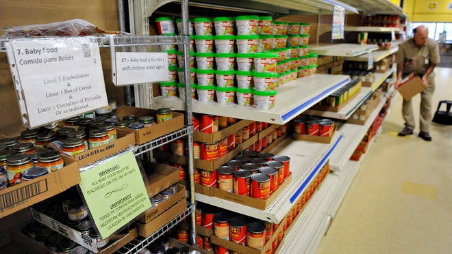 Volunteer Al Brixius and others were busy last month stocking the shelves with food at the Catholic Charities food shelf.