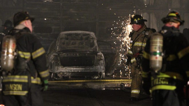 Sparks fly as firefighters work after a fire at a large auto repair garage on W. Seventh St. in New Castle was extinguished.