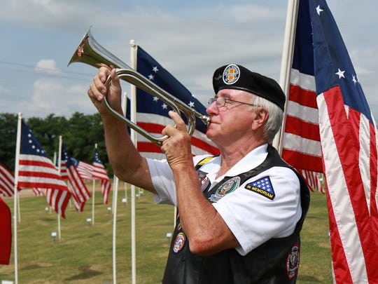 Danny Jackson, member of the Jackson Chapter of the Vietnam Veterans of America, pays tribute at the Field of Flags dedication on Saturday.