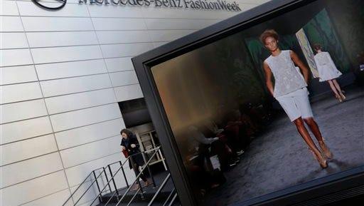 In this file photo, a designer's runway show is shown on a television screen outside the Fashion Week venue at New York's Lincoln Center. The city of New York and Lincoln Center is evicting the invitation-only, twice-yearly Fashion Week in a court spat over destroyed trees and displaced park benches.