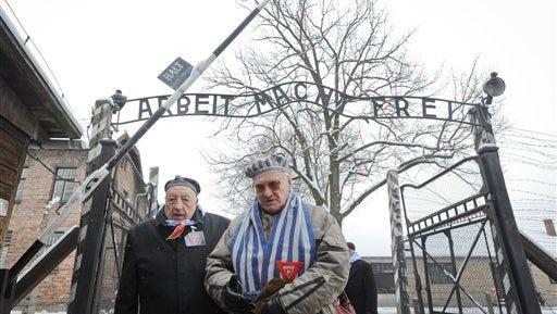 Holocaust survivors walk outside the gate of the of the Auschwitz Nazi death camp in Oswiecim, Poland,  on Tuesday, Jan. 27, 2015. About 300 Holocaust survivors traveled to Auschwitz for the 70th anniversary of the death camp's liberation by the Soviet Red Army in 1945.