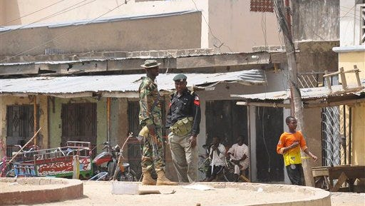 Security forces stand guard at the site of bomb explosion at a market in Maiduguri, Nigeria, Saturday, March 7, 2015 .Two blasts killed more than 10 people on Saturday in a busy marketplace in Maiduguri, the biggest city in northeastern Nigeria, say witnesses. (AP Photo/Jossy Ola)