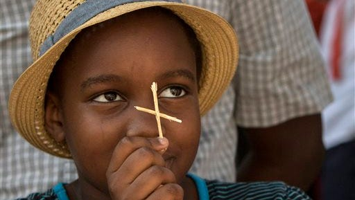 Kristina Kasyoky, of Raleigh, N.C., holds a straw cross she made outside the Emanuel A.M.E. Church, Sunday, June 21, 2015, in Charleston, S.C., four days after a mass shooting at the church claimed the lives of its pastor and eight others.