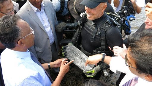 FILE -  In this file photo taken Thursday, May, 7, 2015 underwater explorer Barry Clifford, right, presents a silver bar he believes is part of the treasure of the pirate Captain Kidd, to the president of Madagascar, Hery Rajaonarimampianina, left, on Sainte Marie Island, Madagascar. (AP Photo/Martin Vogl-File)