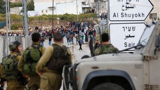 "Israeli soldiers and Palestinians stand at the scene of a stabbing attack, in the West Bank settlement of Kiryat Arba, Monday, Oct. 26, 2015. The Israeli military said a Palestinian stabbed an Israeli in the West Bank before being shot and killed. According to the military, the Israeli was stabbed in the neck Monday and ""severely wounded"" near the city of Hebron. (AP Photo/Wisam Hashlamoun)"