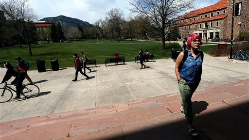 In this April 20, 2015 file photo, students walk to and from classes on the campus quad of the University of Colorado, in Boulder, Colo. There's good news and bad news in the $27 billion state budget up for debate Thursday, March 31, 2016, in the Colorado House. Schools and colleges aren't getting budget cuts. Colleges and vocational training programs fared well, too, getting an extra $14.5 million despite warnings from legislative Democrats that Colorado's 31 public institutions of higher education would see budget cuts requiring tuition hikes. (AP Photo/Brennan Linsley, File)
