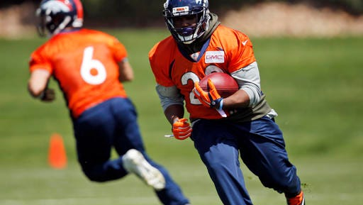 Denver Broncos running back C.J. Anderson, front, runs with the ball after taking a handoff from quarterback Mark Sanchez during NFL football practice Tuesday, May 24, 2016, at the team's headquarters in Englewood, Colo. (AP Photo/David Zalubowski)