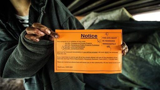 In this Tuesday, May 17, 2016 photo, a homeless woman holds the notice she found on her tent after returning to her camp under the Nevada Street bridge in Colorado Springs, Colo. Far too few shelter beds exist in El Paso County, leaving homeless people with little choice but to risk their safety and break a city ordinance by camping.  (Christian Murdock/The Gazette via AP) MAGS OUT; MANDATORY CREDIT