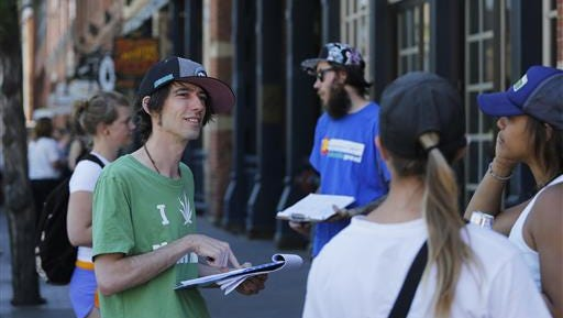 In this June 2016 photo, Robert Cleary, left, a marijuana reform advocate with the group NORML, talks with passersby, gathering signatures on a petition to get a pot club initiative on the ballot in the next election in Denver.