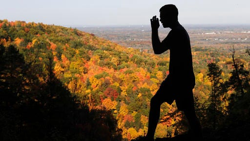 A hiker takes in the fall colors as he makes his way along the Indian Ladder Trail on a warm fall day at John Boyd Thacher State Park, Tuesday, Oct. 18, 2016, in Voorheesville, N.Y.
