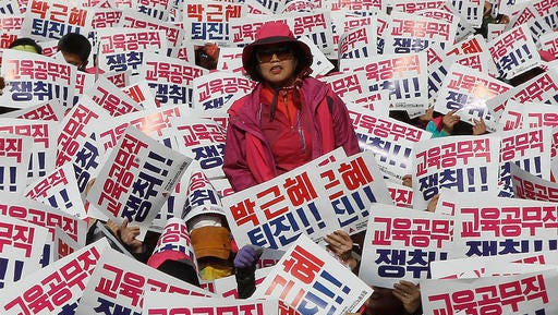 """A South Korean protester stands as her colleagues hold up cards during a rally calling for South Korean President Park Geun-hye to step down in Seoul, South Korea, Saturday, Nov. 12, 2016. Tens, and possibly hundreds, of thousands of South Koreans were expected to rally in Seoul on Saturday demanding the ouster of Park in what would be one of the biggest protests in the country since its democratization about 30 years ago. The signs read """"Park Geun-hye should step down."""""""