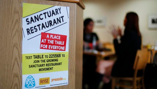 """In this Wednesday, Jan. 18, 2017 photo, a sanctuary restaurant sign is shown at Russell Street Deli in Detroit. Dozens of restaurants are seeking """"sanctuary"""" status, a designation owners hope will help protect employees in an immigrant-heavy industry and tone down fiery rhetoric sparked by the presidential campaign."""