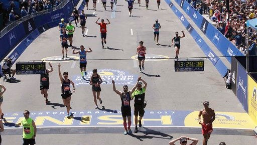 Runners cross the finish line in the 121st Boston Marathon on Monday, April 17, 2017, in Boston. (AP Photo/Charles Krupa)