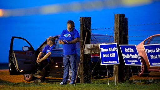 "Anti-death penalty supporters Abraham Bonowitz, left, and Randy Gardner wait near their taped off ""protest corral"" outside the Varner Unit late Monday, April 17, 2017 near Varner, Ark."