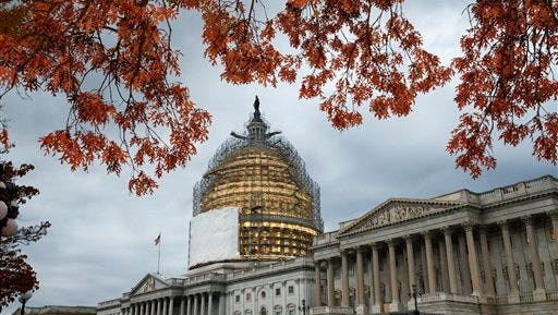 This Nov. 13 file photo shows the U.S. Capitol Dome, in Washington, surrounded by scaffolding for a long-term repair project, and framed by the last of autumn's colorful leaves.  Like a student who waited until the night before a deadline, lawmakers resuming work Monday will try to cram two years of leftover business into two weeks while avoiding a government shutdown.
