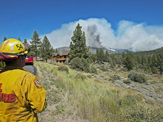 A firefighter monitors a fire in Markleeville, Calif. Several campgrounds have been evacuated, and some highways have been closed due to the fire.