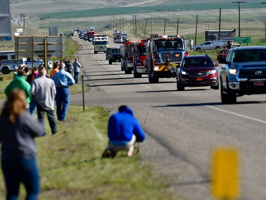 People line Highway 287, as the procession for slain Broadwater County Deputy Mason Moore travels to the memorial service in Belgrade. Moore, a Montana sheriff's deputy who was killed in the line of duty last week, was remembered as a family man, a man of faith and a dedicated public servant who could be tough when he needed to be but still played dolls with his daughter. (Thom Bridge/Independent Record via AP)