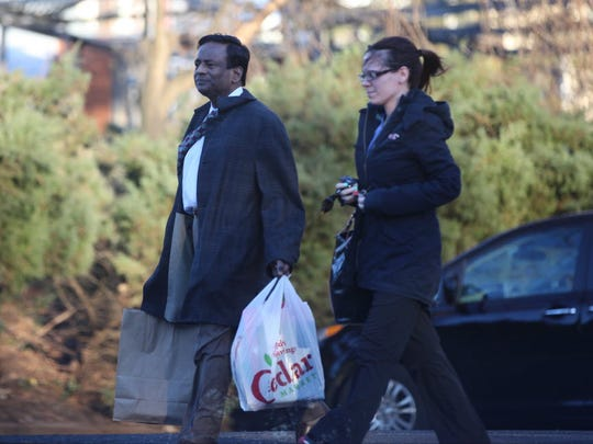 Dr. Gangaram Ragi walks towards his car, beside an unidentified woman, from his Palisade Ave. office in Teaneck on Tuesday, March 17, 2015.