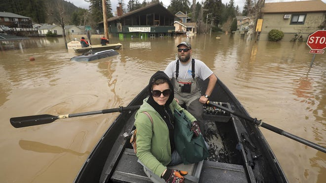 Scott Heemstra takes Veronica Burdette out of the flood zone as floodwaters rise along Mill Street in Guerneville, Calif., Feb. 27, 2019.